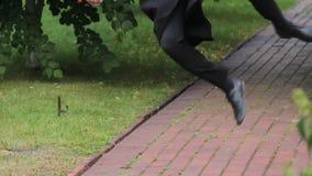 Uomo piacevole in diploma accademico della tenuta del vestito, camminante e saltante nel parco archivi video