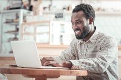 Uomo piacevole felice che usando il netbook Fotografia Stock