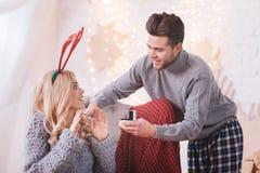Uomo piacevole positivo che mostra alla sua amica un anello di fidanzamento Fotografia Stock Libera da Diritti