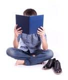 Uomo a piedi nudi che legge un libro fotografie stock