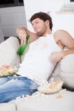 Uomo pigro che si siede sullo strato Fotografia Stock Libera da Diritti