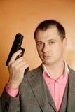 Uomo in pistola della holding del vestito Fotografia Stock