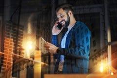 Uomo positivo che parla sul telefono e che esamina il suo aggeggio Immagine Stock