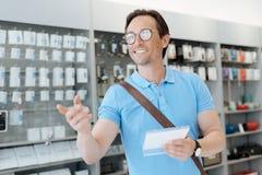 Uomo positivo che sorride e che indica il suo dito al deposito di elettronica Immagine Stock Libera da Diritti