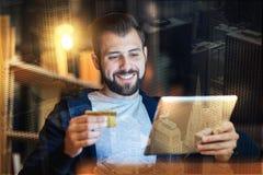 Uomo positivo che sorride mentre facendo spesa online Fotografia Stock