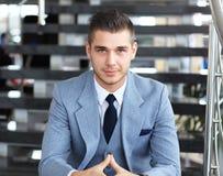 Uomo positivo di affari che si siede sulle scale dell'ufficio moderno fotografia stock libera da diritti