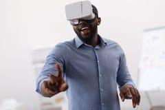 Uomo positivo piacevole che esamina lo schermo virtuale Immagini Stock Libere da Diritti