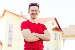 Uomo positivo sulla nuova casa del fondo Immagini Stock