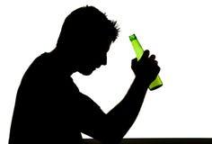 Uomo potabile alcoolizzato con la bottiglia di birra nella siluetta di dipendenza di alcool Fotografia Stock