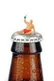 Uomo potabile miniatura su una bottiglia della bottiglia da birra Immagini Stock