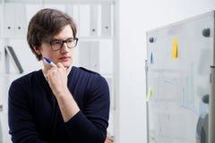 Uomo premuroso che esamina i grafici di affari Fotografia Stock