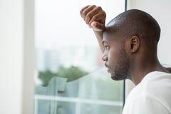 Uomo premuroso che guarda fuori la finestra Fotografia Stock Libera da Diritti