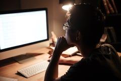 Uomo premuroso che lavora con il computer dello schermo in bianco nella stanza scura Immagini Stock