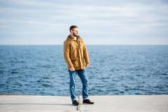Uomo premuroso che sta sul pilastro vicino al mare Fotografie Stock