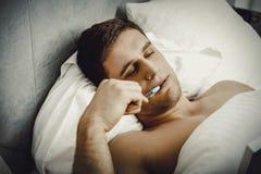 Uomo premuroso con una nota nel suo letto Immagini Stock
