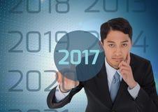 Uomo premuroso di affari nel fondo digitalmente generato che tocca 2017 immagine stock libera da diritti
