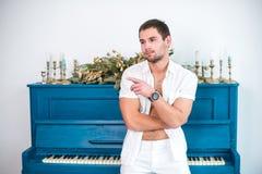 Uomo premuroso e bello con una barba in vestiti bianchi contro lo sfondo di un piano, una camicia raspata con un torso nudo Fotografia Stock Libera da Diritti