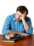 Uomo premuroso vicino ad un mucchio di vecchi libri Fotografie Stock Libere da Diritti