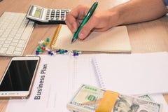 Uomo, prendente le note Uomo con i dollari, contanti sulla tavola Profitti, fotografie stock