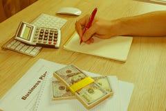 Uomo, prendente le note Uomo con i dollari, contanti sulla tavola Profitti, fotografie stock libere da diritti
