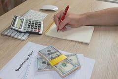 Uomo, prendente le note Uomo con i dollari, contanti sulla tavola Profitti, risparmio Pila di dollari Successo, motivazione, flus immagine stock