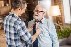 Uomo preoccupantesi che aiuta suo padre anziano a legare il suo legame immagine stock