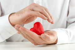 Uomo preoccupantesi che foggia a coppa un cuore rosso in sue mani Fotografie Stock