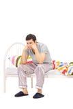 Uomo preoccupato che si siede su un letto e che contempla Immagini Stock