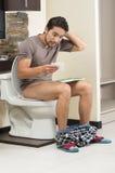 Uomo preoccupato che si siede sull'esaurire della toilette Fotografia Stock Libera da Diritti