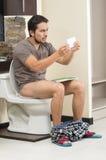 Uomo preoccupato che si siede sull'esaurire della toilette Fotografia Stock
