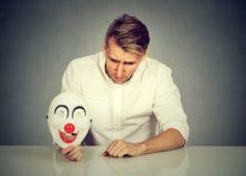 Uomo preoccupato con la maschera triste del pagliaccio della tenuta di espressione che esprime allegria fotografia stock
