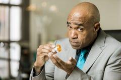 Uomo preoccupato con una bottiglia di prescrizione dell'oppioide Immagini Stock Libere da Diritti