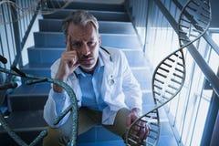 Uomo preoccupato di medico che si siede con i fili del DNA 3D Immagine Stock