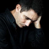 Uomo preoccupato e depresso isolato sul nero Fotografia Stock