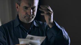 Uomo preoccupato e sollecitato che esamina le fatture video d archivio