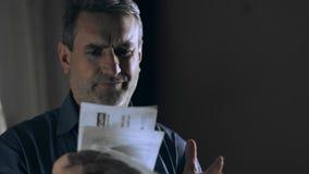 Uomo preoccupato e sollecitato che esamina le fatture e che le getta sul pavimento video d archivio