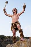 Uomo primitivo che sta su una roccia Immagini Stock