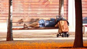 Uomo privo che dorme su un banco in un parco Concetto senza tetto e sociale di problema spazio vuoto della copia fotografia stock libera da diritti