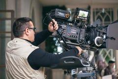 Uomo professionale della macchina fotografica sul lavoro fotografia stock