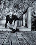 Uomo professionale seduto sul decking del giardino immagine stock