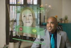 Uomo professionale sorridente che ha conversazione telefonica facendo uso di un Futur Immagine Stock Libera da Diritti