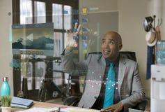 Uomo professionale sorridente che seleziona cartella un computer futuristico immagini stock libere da diritti