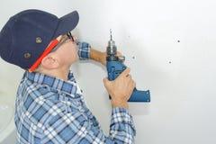 Uomo pronto a perforare parete con il perforatore fotografia stock libera da diritti