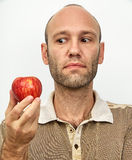 Uomo questioningly che esamina mela rossa Immagine Stock Libera da Diritti