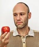 Uomo questioningly che esamina mela rossa Fotografia Stock Libera da Diritti