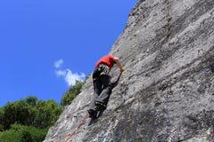 Uomo rampicante di sport su una parete della roccia fotografia stock