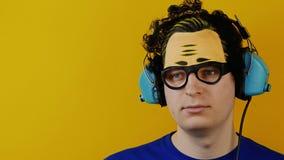 Uomo riccio in modo divertente che ascolta la musica in retro cuffie o cuffie archivi video