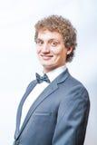 Uomo riccio sorridente in nero e cravatta a farfalla Fotografia Stock