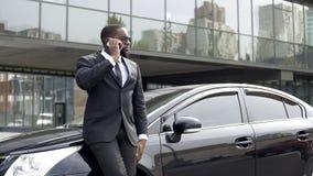 Uomo ricco serio in vestito costoso che discute a fondo telefono in grande città fotografia stock libera da diritti