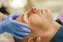 Uomo rilassato che ha un massaggio di fronte e un trattamento della sbucciatura immagine stock libera da diritti